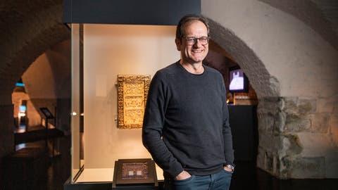 Cornel Dora im Gewölbekeller der Stiftsbibliothek, vor dem kostbaren, mit Elfenbein und Gold verziertem  «Evangelium longum». ((Bild: Ralph Ribi))