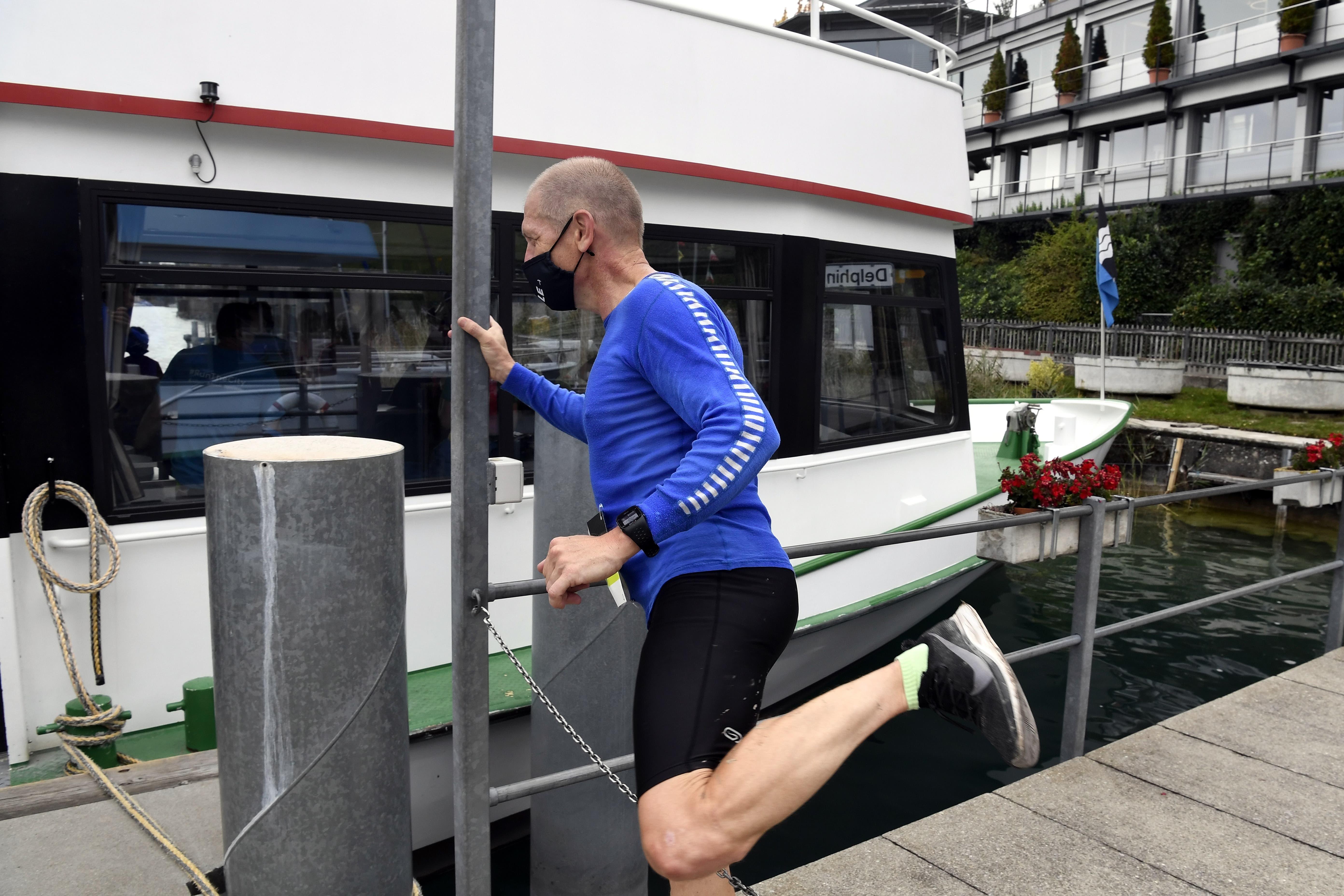 Läufer gehen mit Masken auf das Schiff ueber den Hallwilersee.