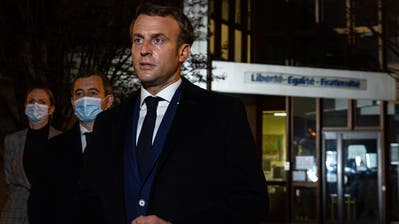 Frankreichs Präsident Emmanuel Macron (r) mit InnenministerGerald Darmanin (2. v.l.), vor der Schule inConflans Saint-Honorine nahe Paris: Hier unterrichtete Samuel Paty, bevor er Ende letzter Woche Opfer eines grausamen Mordanschlags wurde. (Abdulmonam Eassa / Pool / EPA)