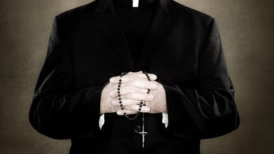 A priest holding prayer beads (Image Source)