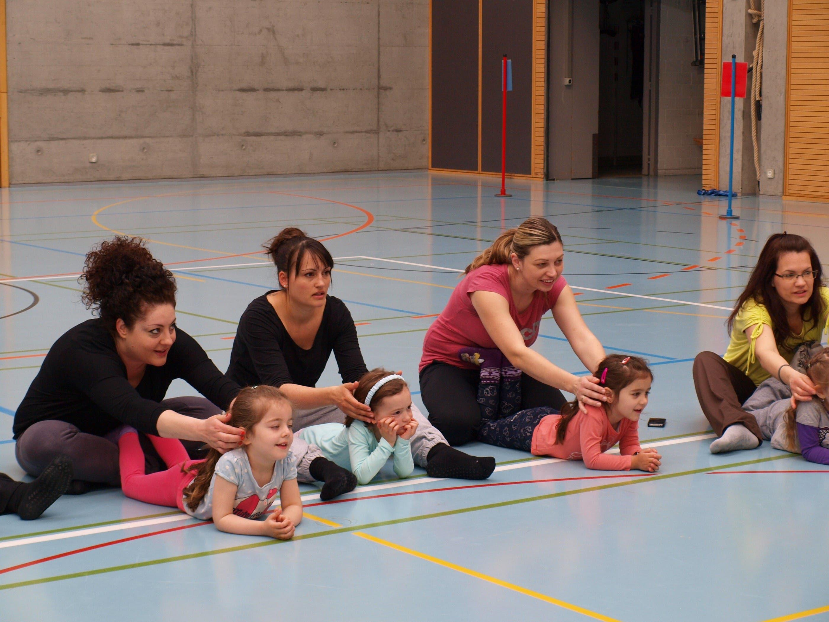 MUKI Die Kinder horchen aufmerksam den Erklärungen der Leiterinnen während sie von ihren Müttern gekrault werden.