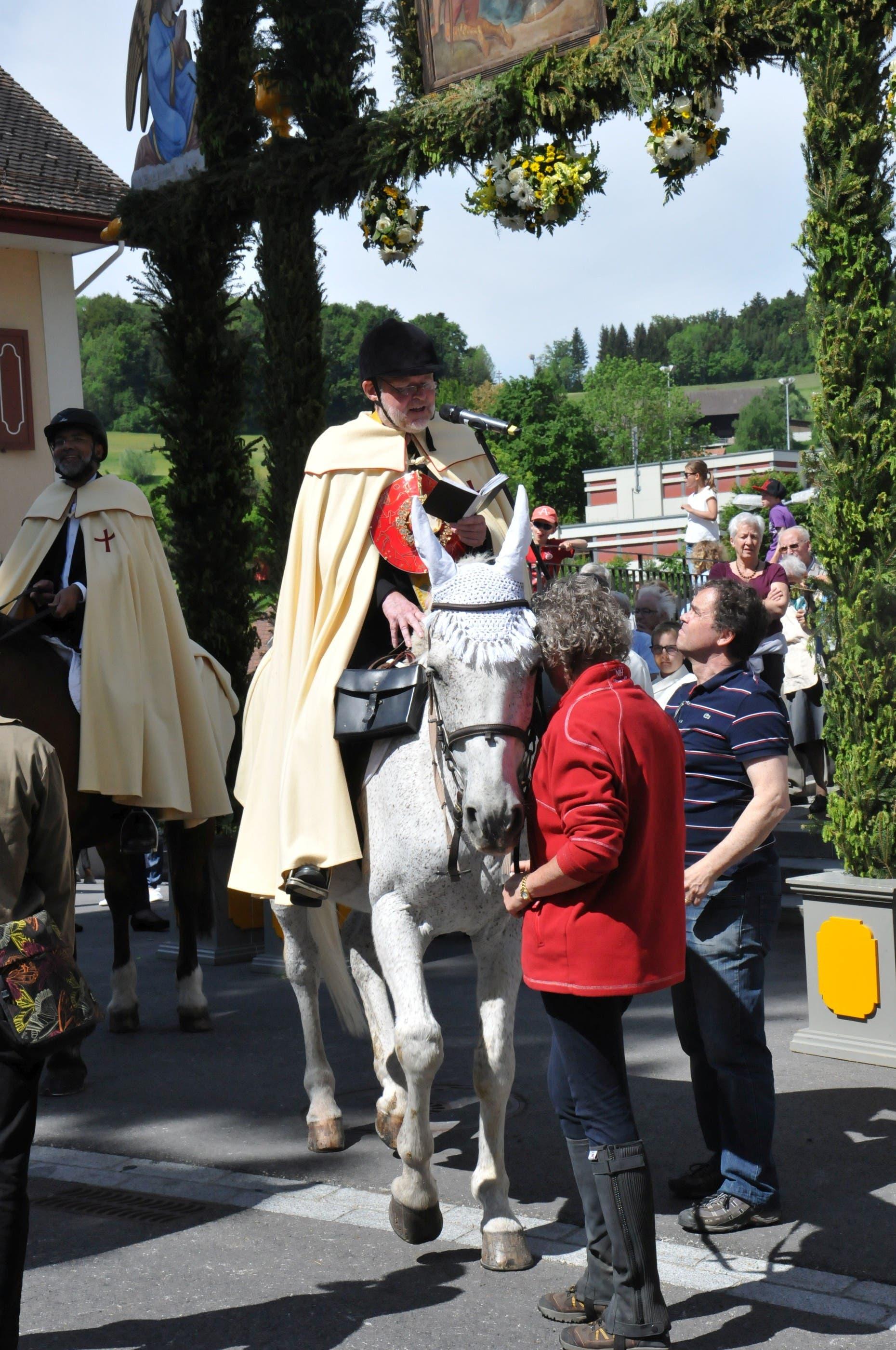 Vor dem Weiterritt wendet sich Pfarrer Helmut Gehmann vor der Kirche in Rickenbach an die Gläubigen
