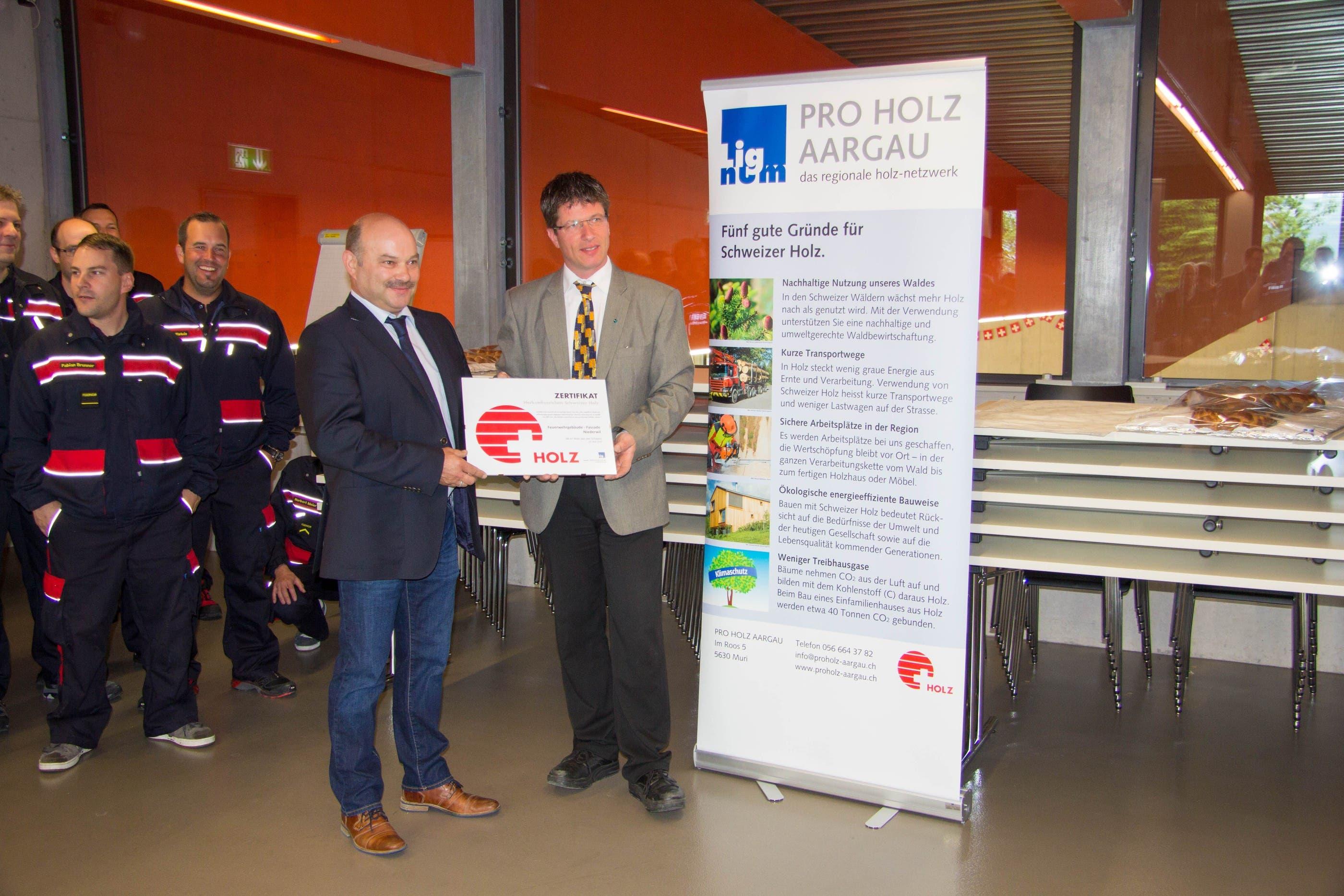 Ein Zertifikat für die Fassade aus einheimischem Holz überreicht Daniel Wehrli von Pro Holz Aargau dem Vizeammann von Niederwil, Peter Gauch