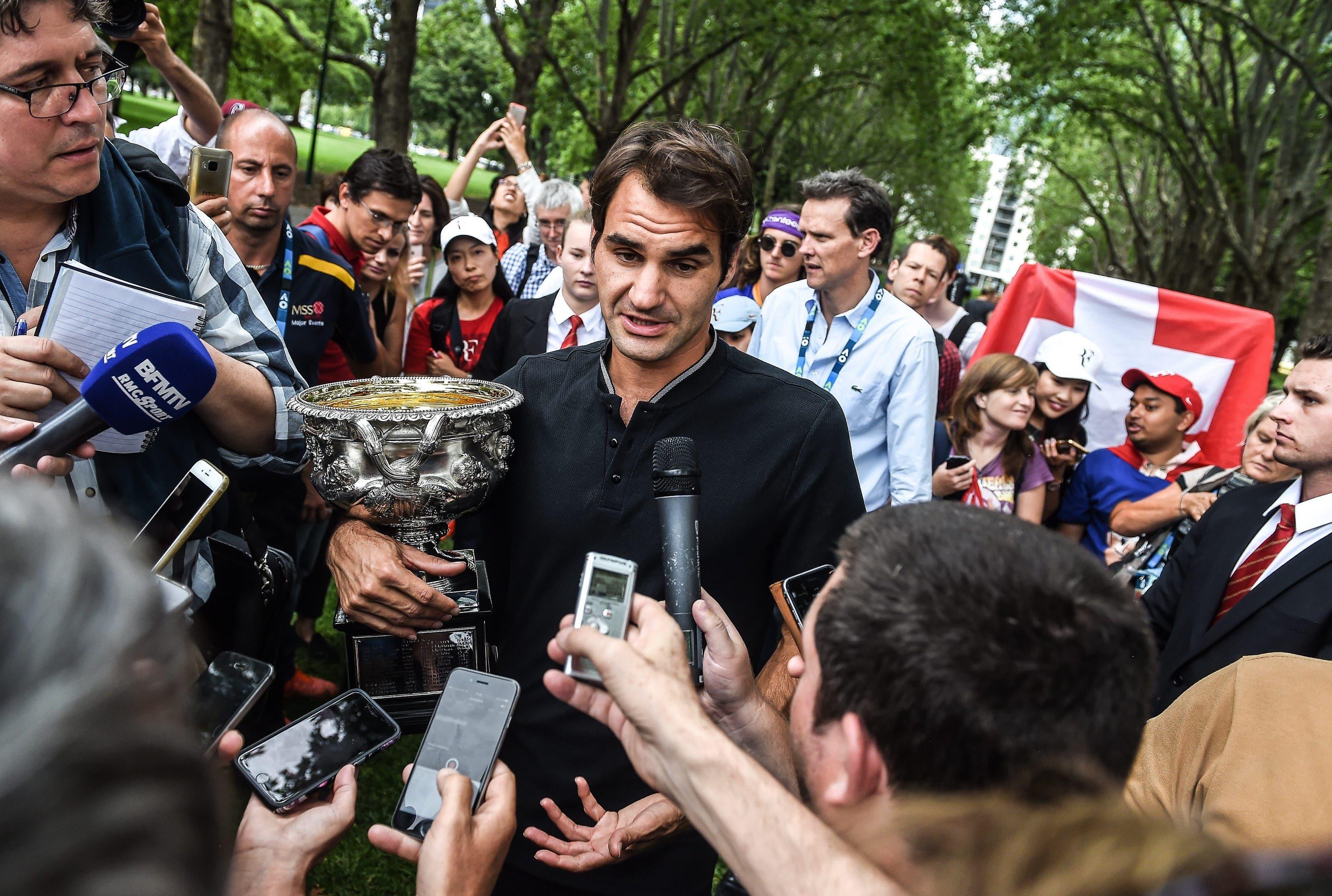 Keine ruhige Minute: Nach seinem sensationellen Turniersieg an den Australian Open wird Roger Federer vor seinem Fototermin in den Carlton Gardens von Journalisten in Beschlag genommen.
