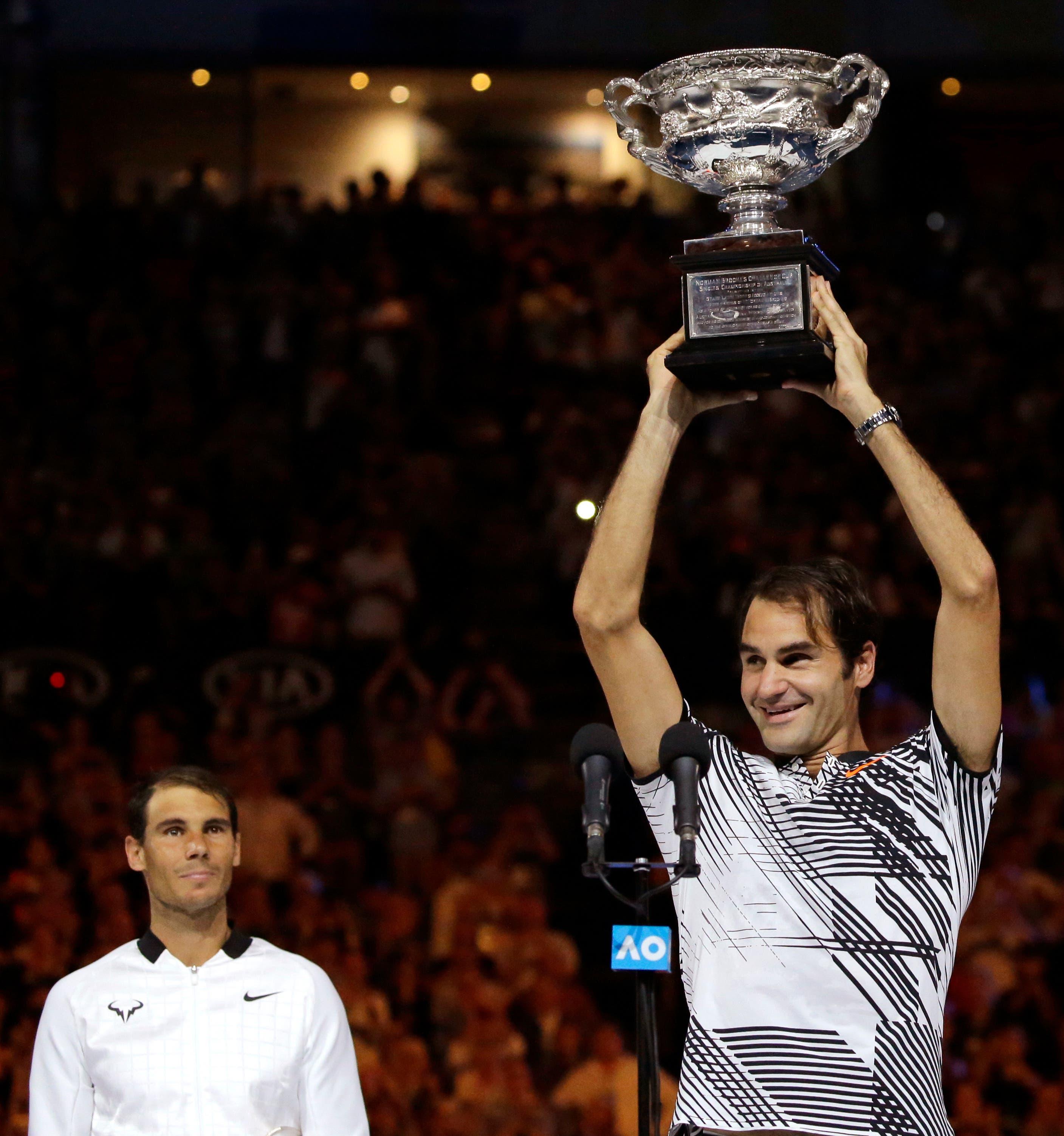 Überglücklich: Roger Federer stemmt den Pokal in die Höhe. Rafael Nadal erweist sich aus sehr fairer Verlierer.