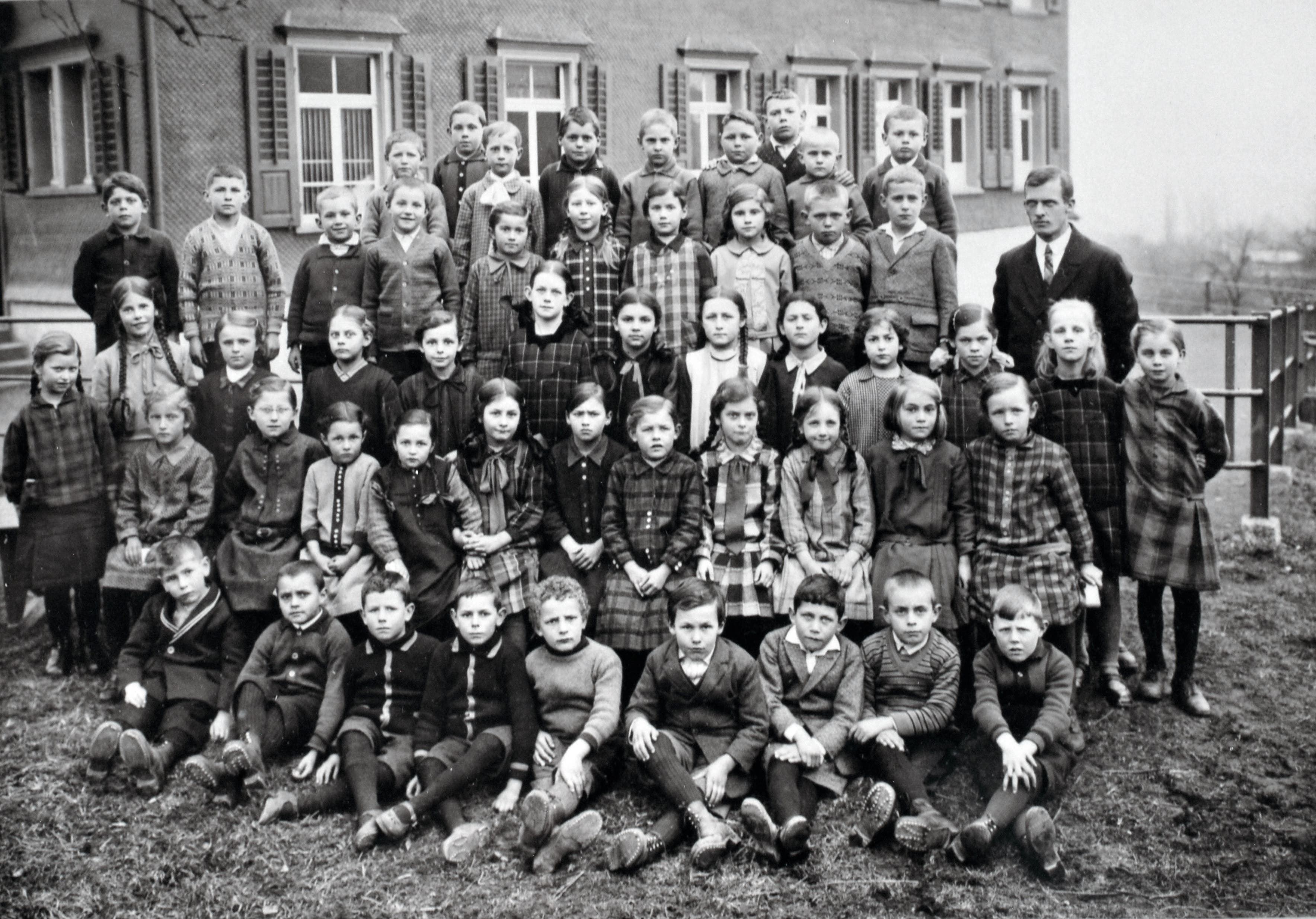 Lehrer Johann Lutziger (rechts) mit seiner Schulklasse um das Jahr 1930 vor dem Studner Schulhaus. Fliessend Wasser, Strom oder eine Turnhalle gab es damals noch nicht. Die Haltung ist nicht mehr so steif, gelächelt haben dennoch nur wenige. Karierte Kleidung scheint in Mode gekommen zu sein.