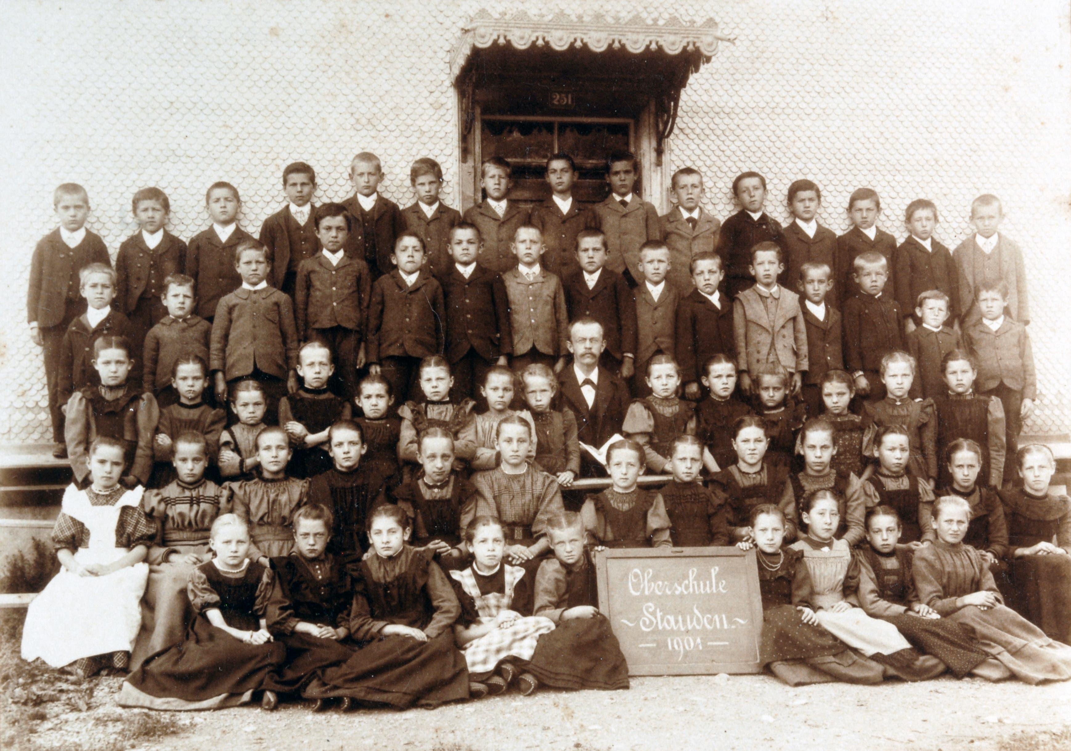 Die «Oberschule Stauden» im Jahr 1901. Man beachte die grosse Anzahl Schülerinnen und Schüler, die Grösse des Lehrers (Mitte), die ernsten Gesichter (auf Fotos zu lachen war unüblich), die aufrechte Haltung und die sonntägliche Kleidung.