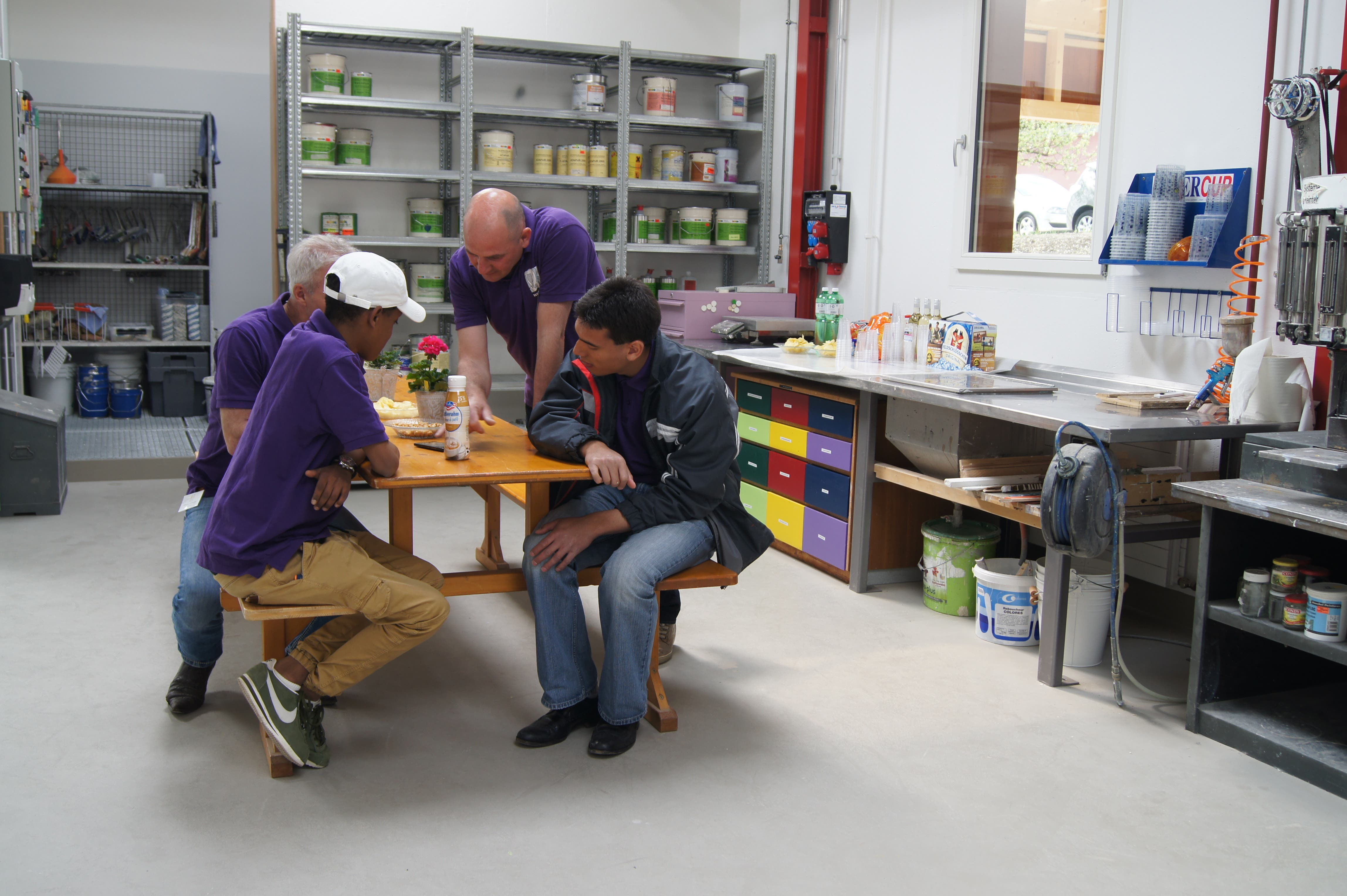 Zwei Lehrlinge (vorne) und ihre Betreuer in der Malerwerkstatt