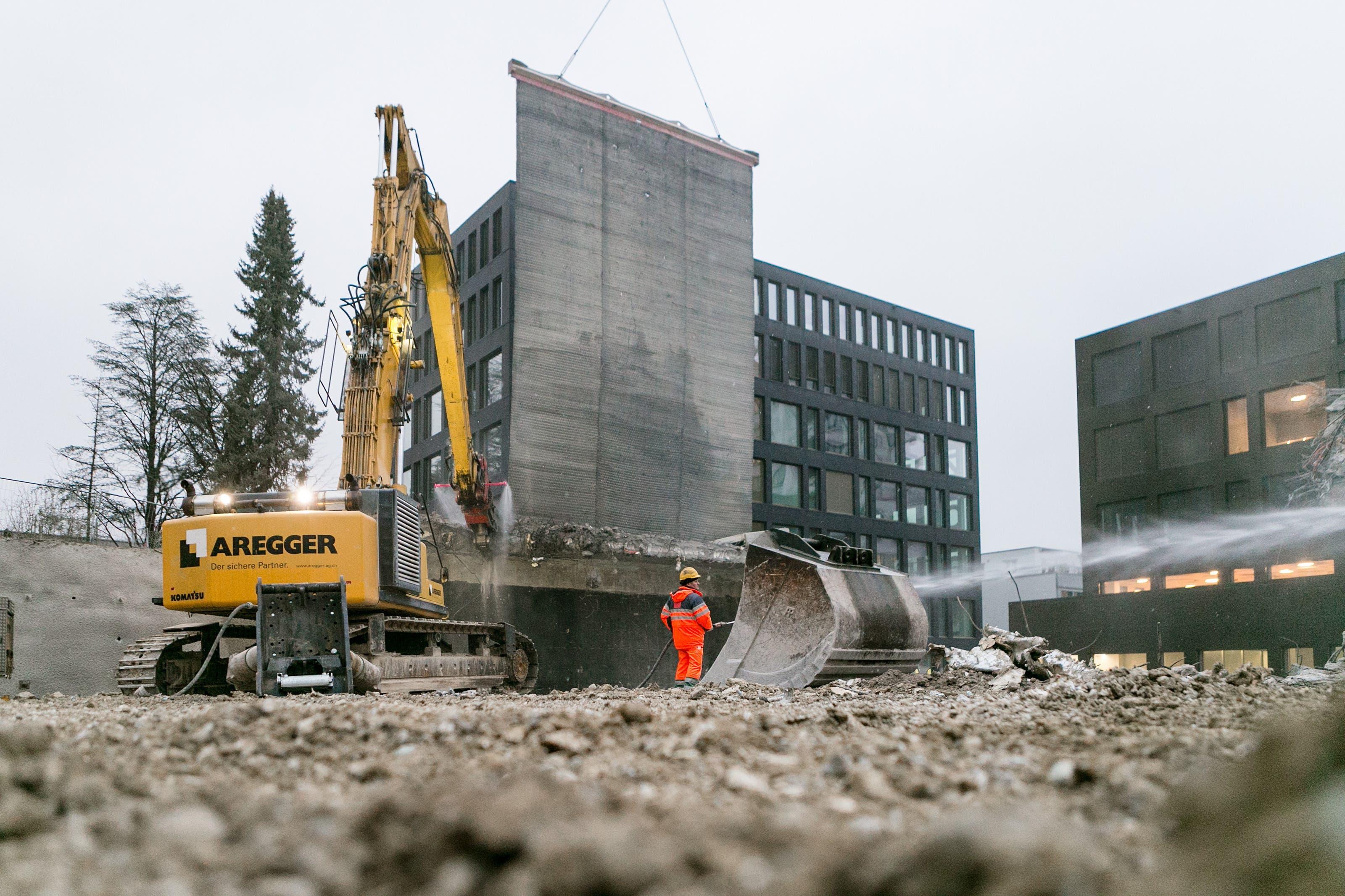 Der Abbruchvorhang schützt die Nachbargebäude, er wiegt rund 16 Tonnen und wird vom Kranwagen in die Luft gehalten.