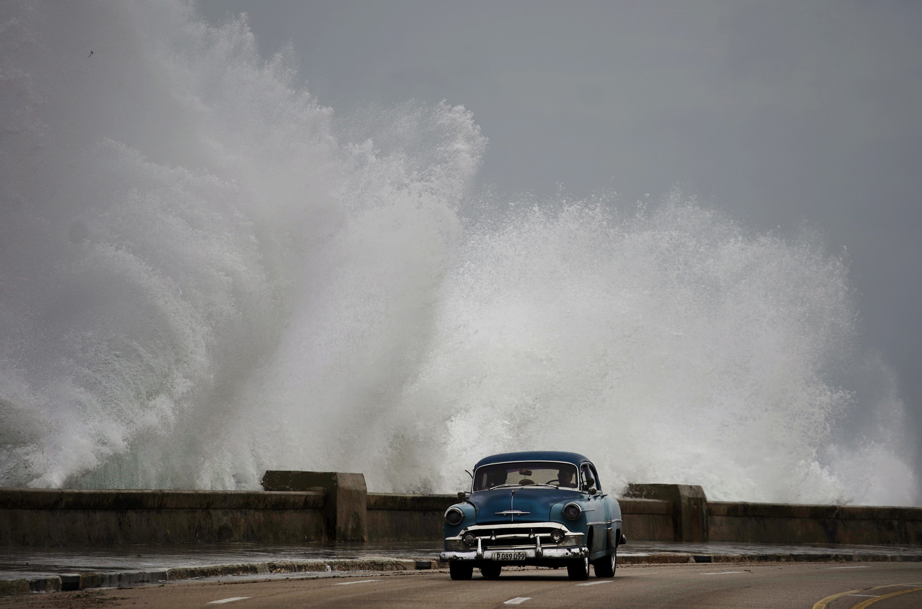 Dieses Foto wurde am 9. Oktober 2018 in Kubas Hauptstadt Havanna aufgenommen. Meterhohe Wellen erreichten die Insel. Waves crash against the Malecon, triggered by the outer bands of Hurricane Michael, as man drives past in a classic American car in Havana, Cuba, Tuesday, Oct. 9, 2018. A fast and furious Hurricane Michael is churning toward the Florida Panhandle with 110 mph winds and a potential storm surge of 12 feet, giving tens of thousands of people precious little time to get out. (AP Photo/Ramon Espinosa