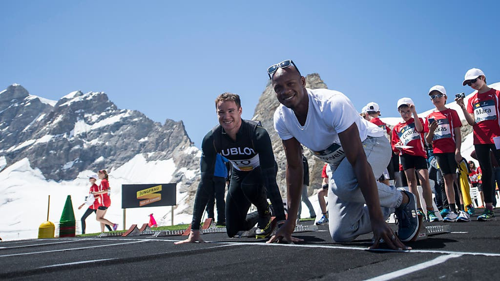 Sprinter Asafa Powell aus Jamaika (rechts) und Langläufer Dario Cologna posieren auf dem Jungfraujoch.