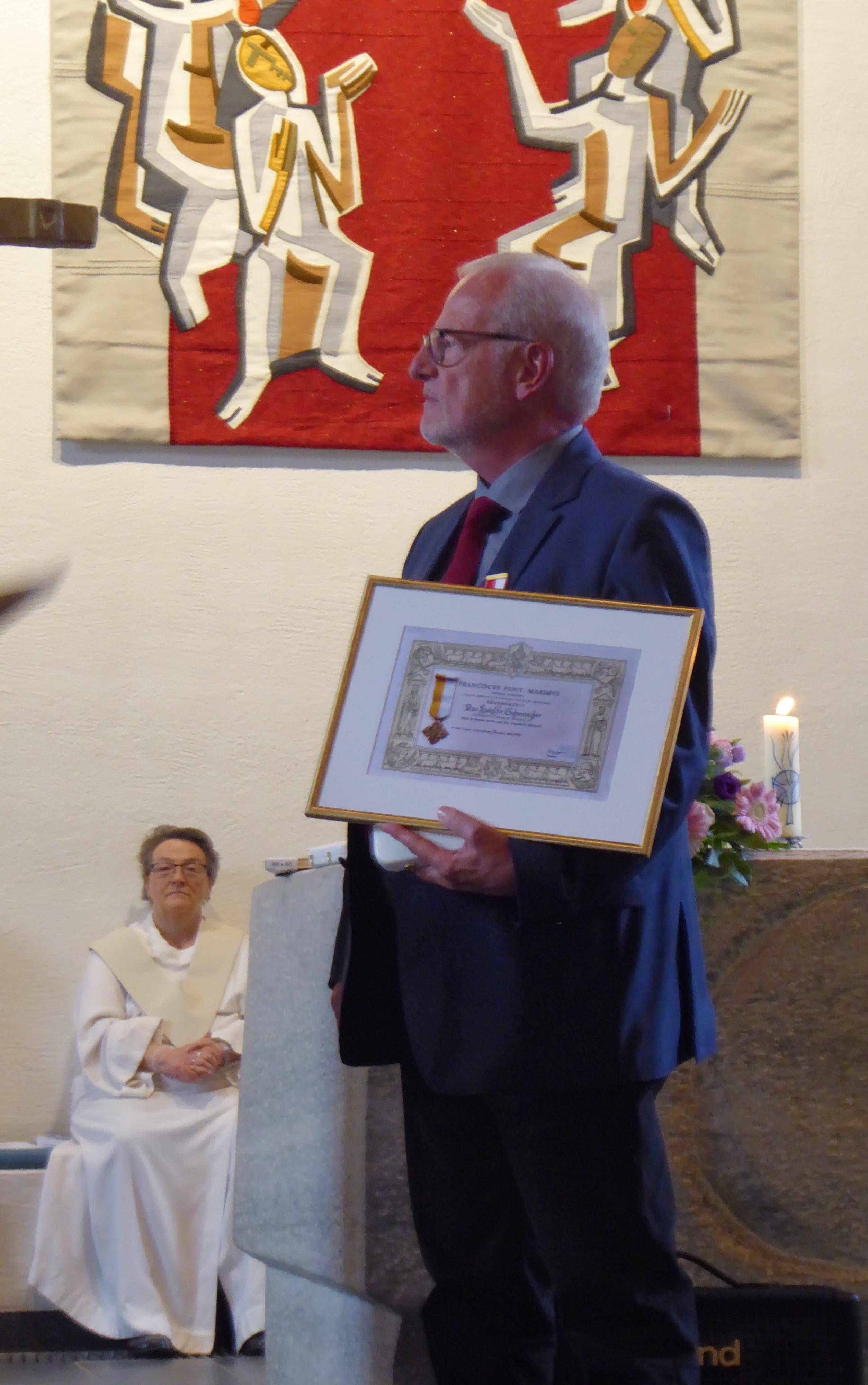 """undefined Chorleiter Ruedi Schumacher mit der päpstlichen Auszeichnung """"Bene merenti"""" für über 40-jähriges Wirken."""