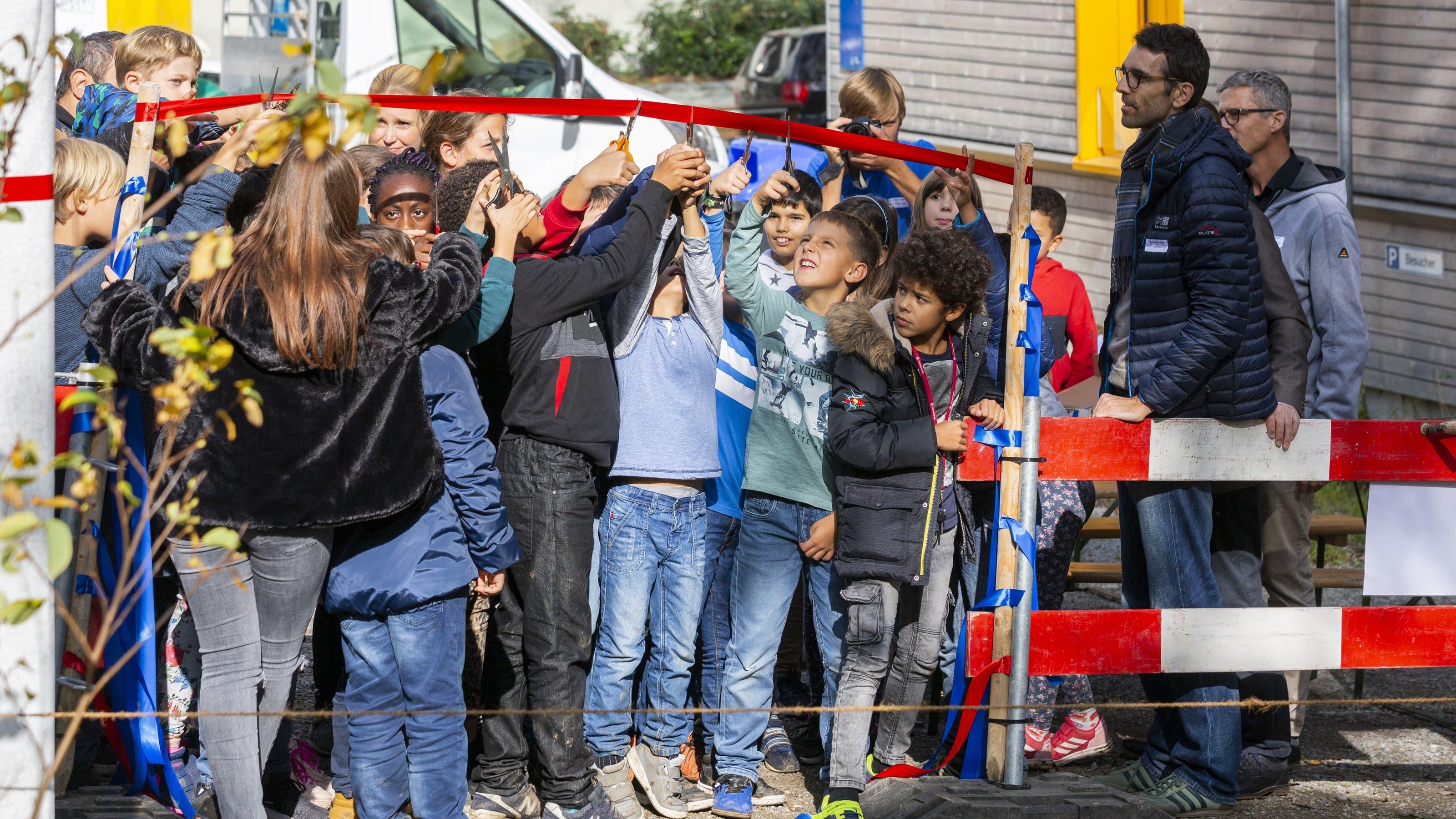 Für die Eröffnung des Spielplatzes wurden mehrere Bänder zerschnitten. Das letzte Band durchtrennten die Kinder.