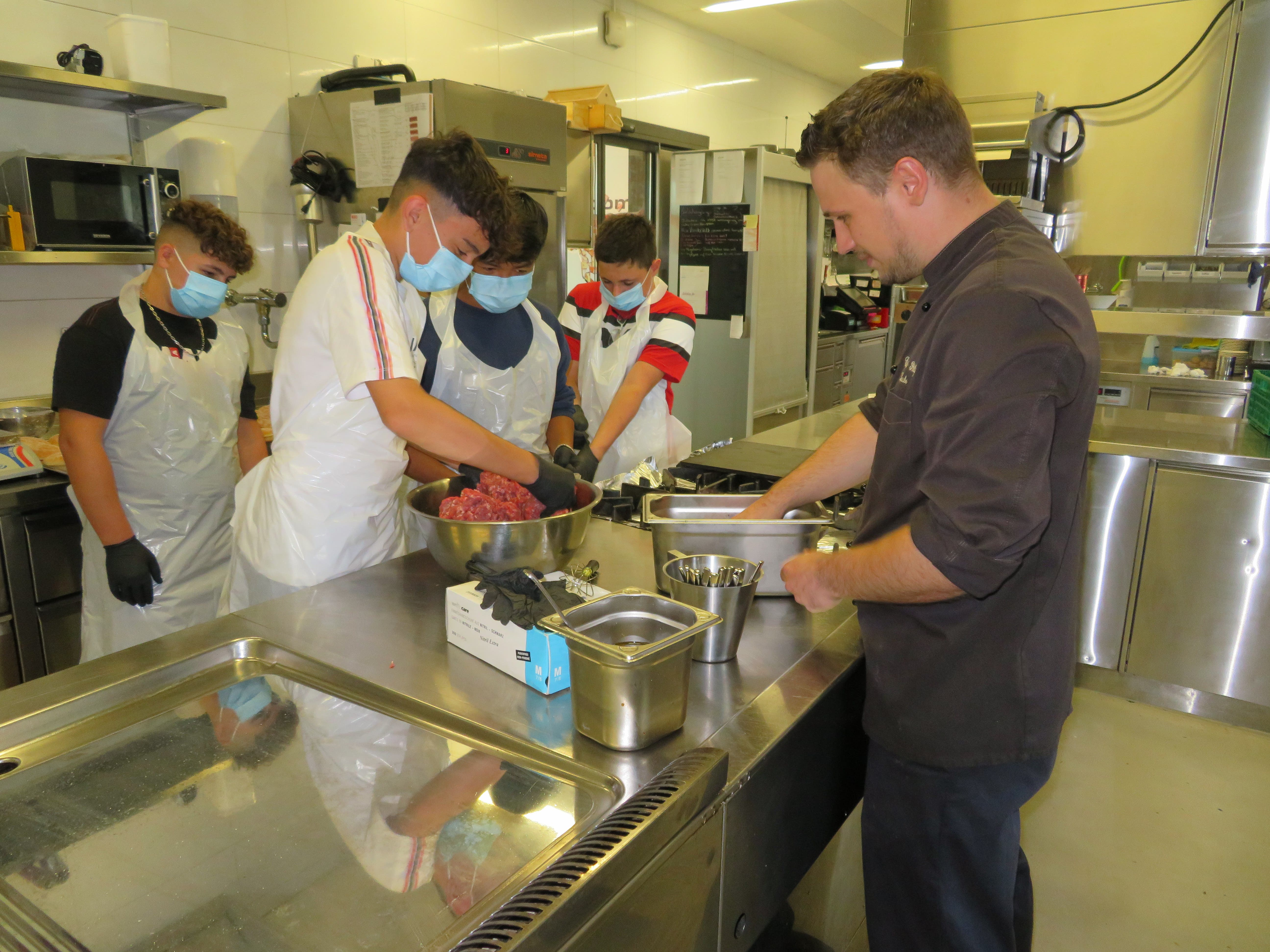 Laube zeigt den Schülern die Zubereitung des Hamburgers.