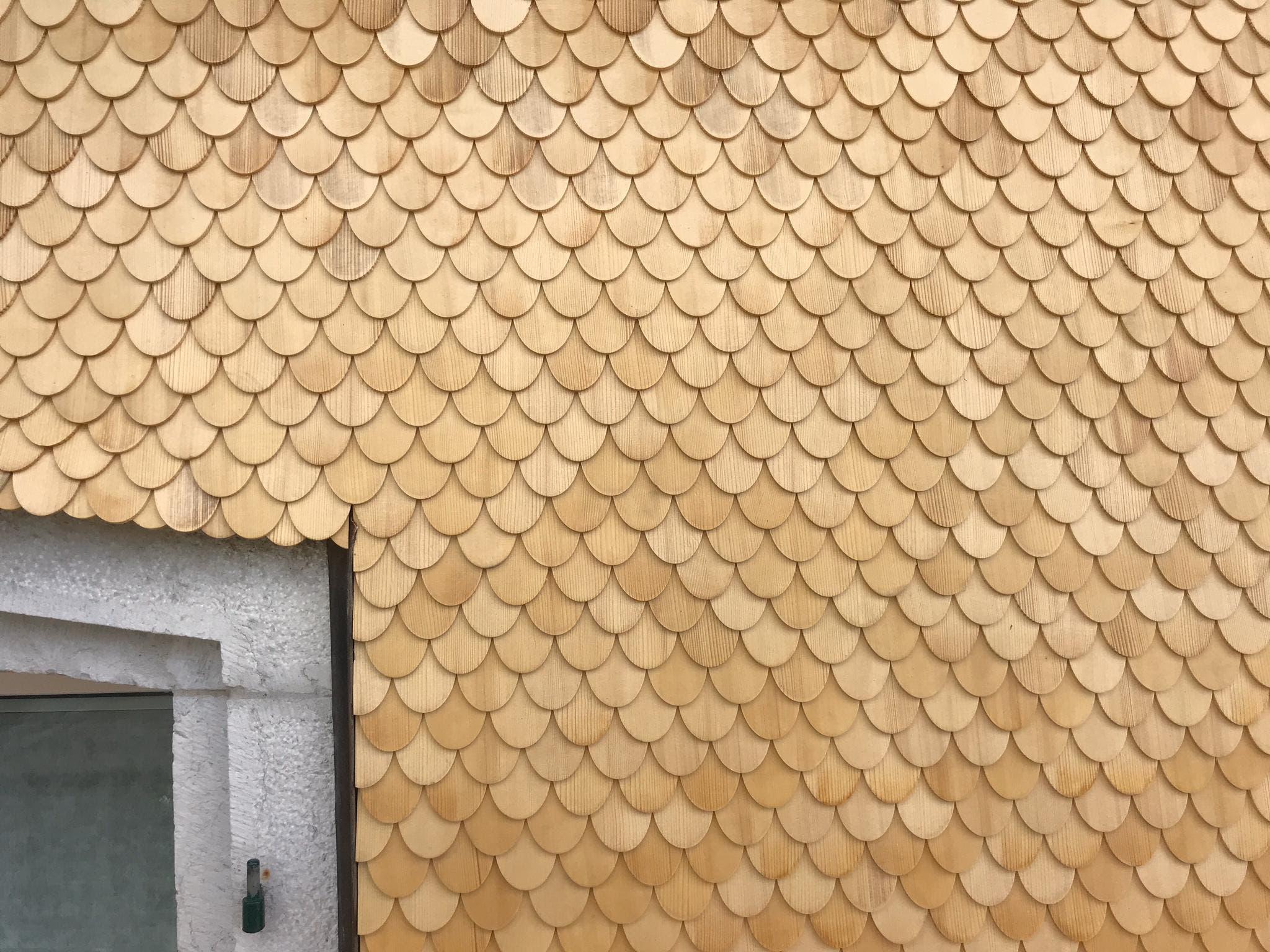 Mit solchen kleinen Holzschindeln wird die West-Fassade des Polizeipostens neu eingedeckt.