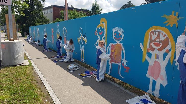 So brachten Schüler Farbe auf die blaue Baustellenwand der Limmattalbahn