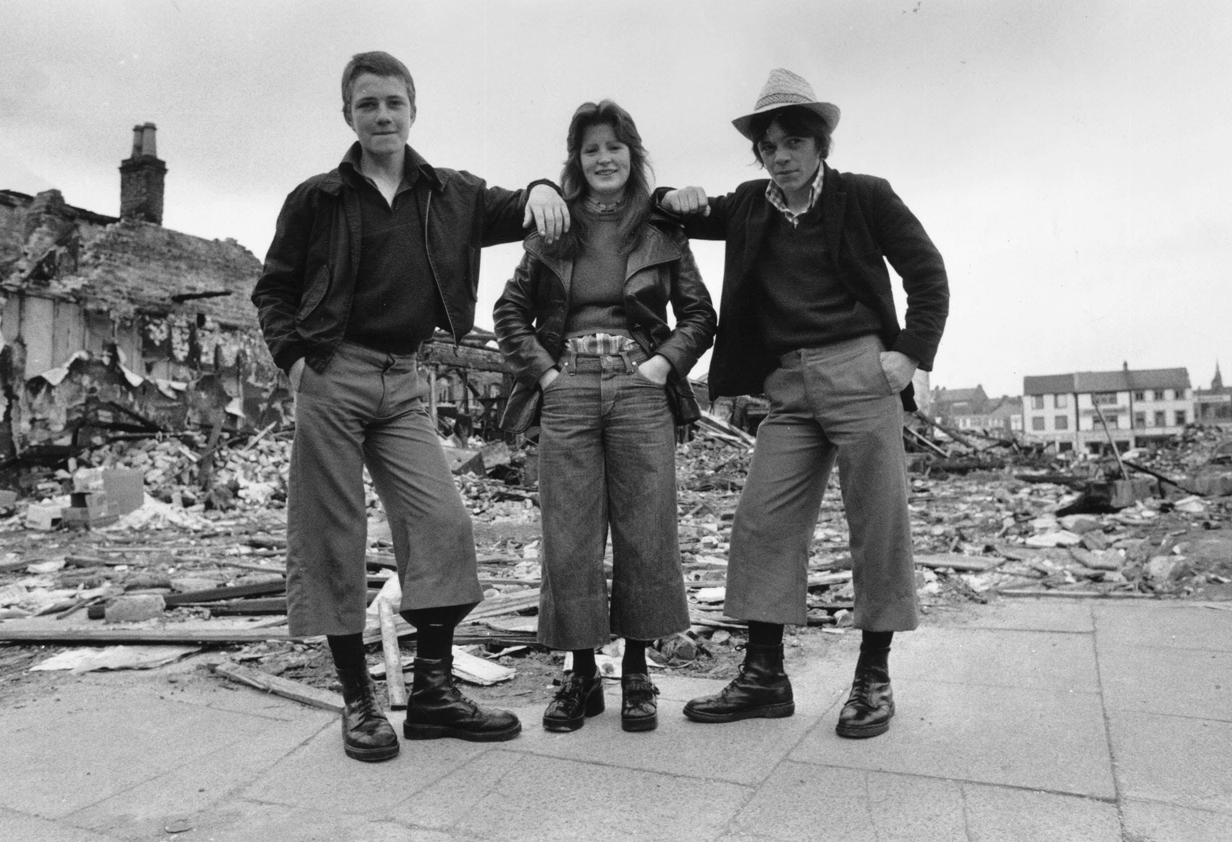 1974: Teenager tragen den neusten Modetrend in Irland: Gekürzte Hose und Doc Martens Stiefeln in den Ruinen von Belfast - und sehen damit gar nicht so anders aus wie modische, junge Frauen und Männer 2020.