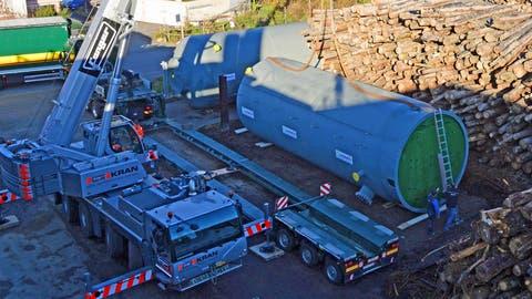 Das Holzheizwerk Chilcherli in Alpnach wird mit zwei je rund 16 Tonnen schweren und rund elf Meter hohen Energiespeichern ausgerüstet. Diese wurden nun angeliefert. Mit einem Fanger-Kran wurden die Speicher von den Sattelschleppern angehoben und beim Brennholzlager deponiert. (Bild:Robert Hess (Alpnach, 18. November 2020))