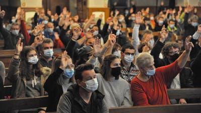 Stimmberechtigte heben ihre Hände zur Abstimmungin der Pfarrkirche Bristen. (Bild: Urs Hanhart (18. November 2020))