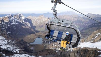 Skifahrer mit Atemschutzmasken sind mit der Luftseilbahn Rotairauf den Titlis unterwegs