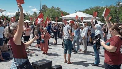 Szene aus dem Film. Corona-Skeptiker zeigen die Verfassung und lauschen der Nationalhymne.