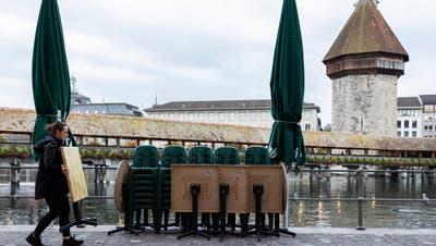 Eine Frau stellt Tische am Reussquai zur Seite. (Bild: Patrick Hürlimann (Luzern, 14. Oktober 2020))