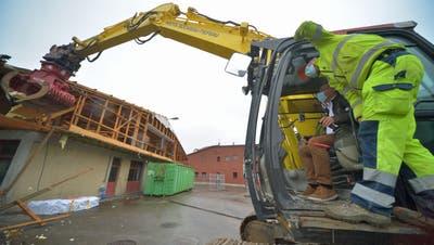 Gemeindepräsident Kilian Germann reisst mit dem Bagger ein erstes Stück der Dachkonstruktion des alten Werkhofs runter. (Bild: Mario Testa (Bürglen, 3. November 2020))