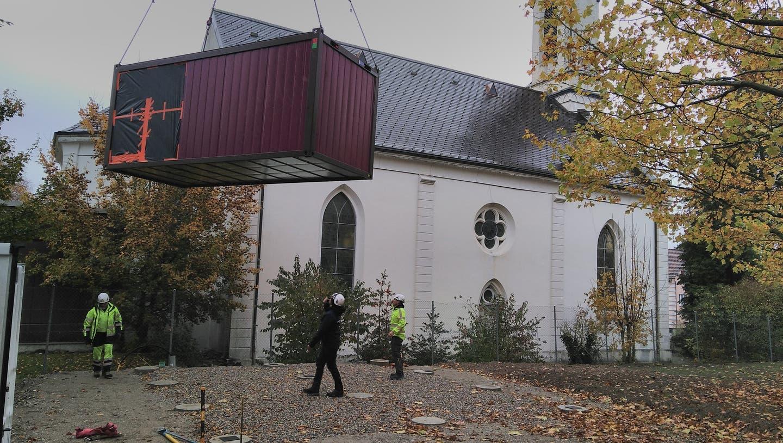 Container wird über das Dach gehoben — die Bauarbeiten für den neuen Spielplatz haben begonnen