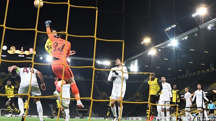 Die Szene des Spiels: Cluj-Goalie Cristian Balgradean faustet vor YB-Verteidiger Cédric Zesiger den Ball weg. (Keystone)