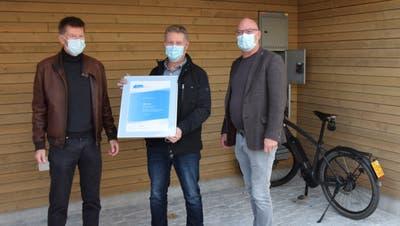 Marcel Sturzenegger, kantonales Amt für Energie (v.l.), Pascal Benz, Präsident Energiekommission Oberriet, und Rolf Huber, Gemeindepräsident Oberriet, bekamen das Energiestadt-Zertifikat vor der neuen E-Bike-Ladestation überreicht. (Bild: gk)