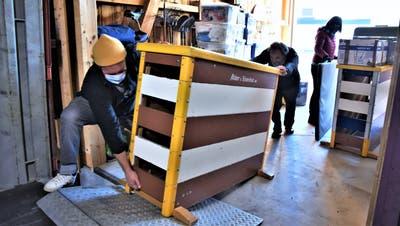Kurt Bucher und Lucas Cadonau schieben eine Schwedenbank in den Schiffscontainer. ((Bild: Roman Scherrer))