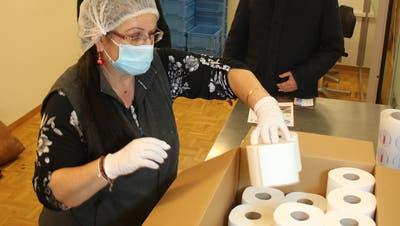 Antonietta D'Angelo verpackt an einem geschützten Arbeitsplatz in der Stiftung Weidli WC-Papier für das Projekt pressant.ch. Hinten im Bild Rita und Beat Barmettler, Mitinitianten des Projekts. (Bild: Marion Wannemacher, Stans, 1. Dezember 2020)