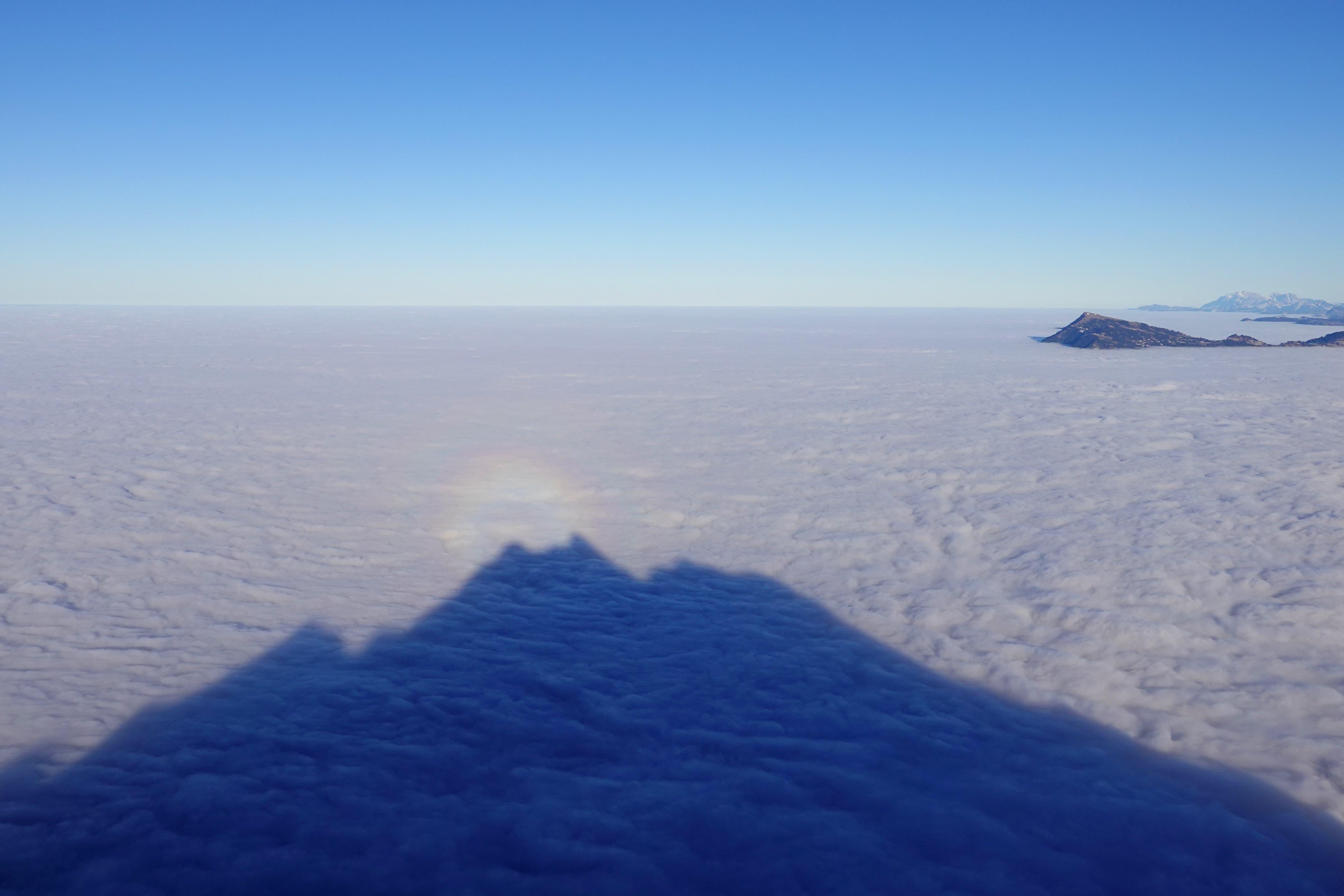 Der Pilatus wirft sein Schattenbild aufs Nebelmeer. Über dem Gipfel auf dem Nebelmeer bildet sich ein kleiner Heiligenschein - ein Halo. Da kann die Rigi nur neidisch hinübergucken.