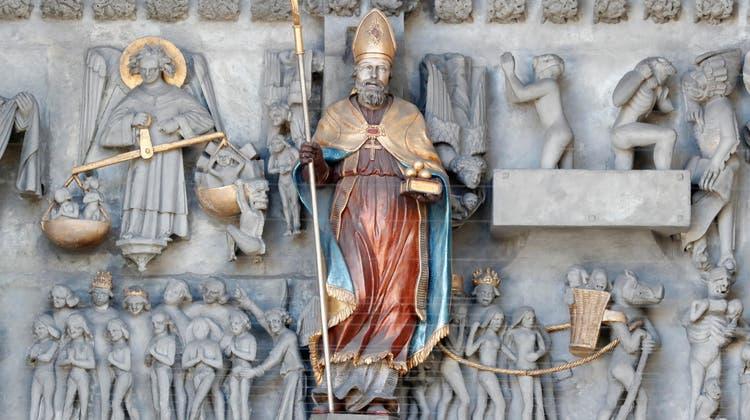 Sankt Nikolaus hält am Portal der Kathedrale von Freiburg (i. Ü.) drei Goldkugeln bereit. (Bild: Alamy)