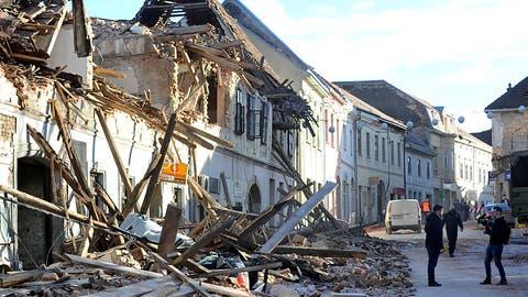 Zwei Passanten machen ein Foto vor den Trümmern eines durch ein Erdbeben eingestürzten Hauses. (Keystone/AP)