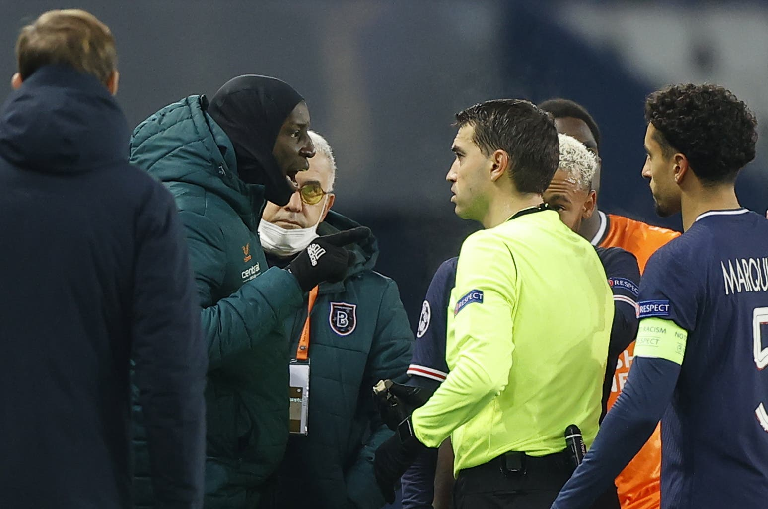 Der Betreuer erhält, weil er sich lauthals beschwert, die rote Karte. Basaksehir-Spieler Demba Ba erklärt den Vorgang dem Schiedsrichter.