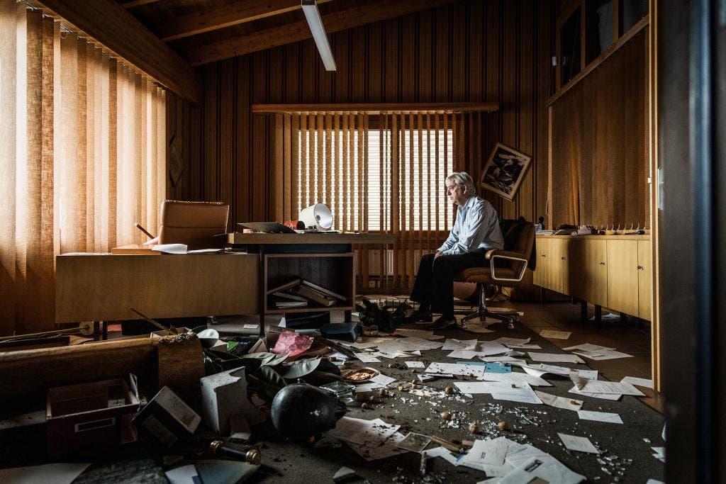 Charles Mulliger (gespielt von Ueli Jäggi), Patron der Sägerei Mulliger, sitzt in einem Scherbenhaufen. Mulligers Sohn Frank hat das Büro seines Vaters verwüstet.