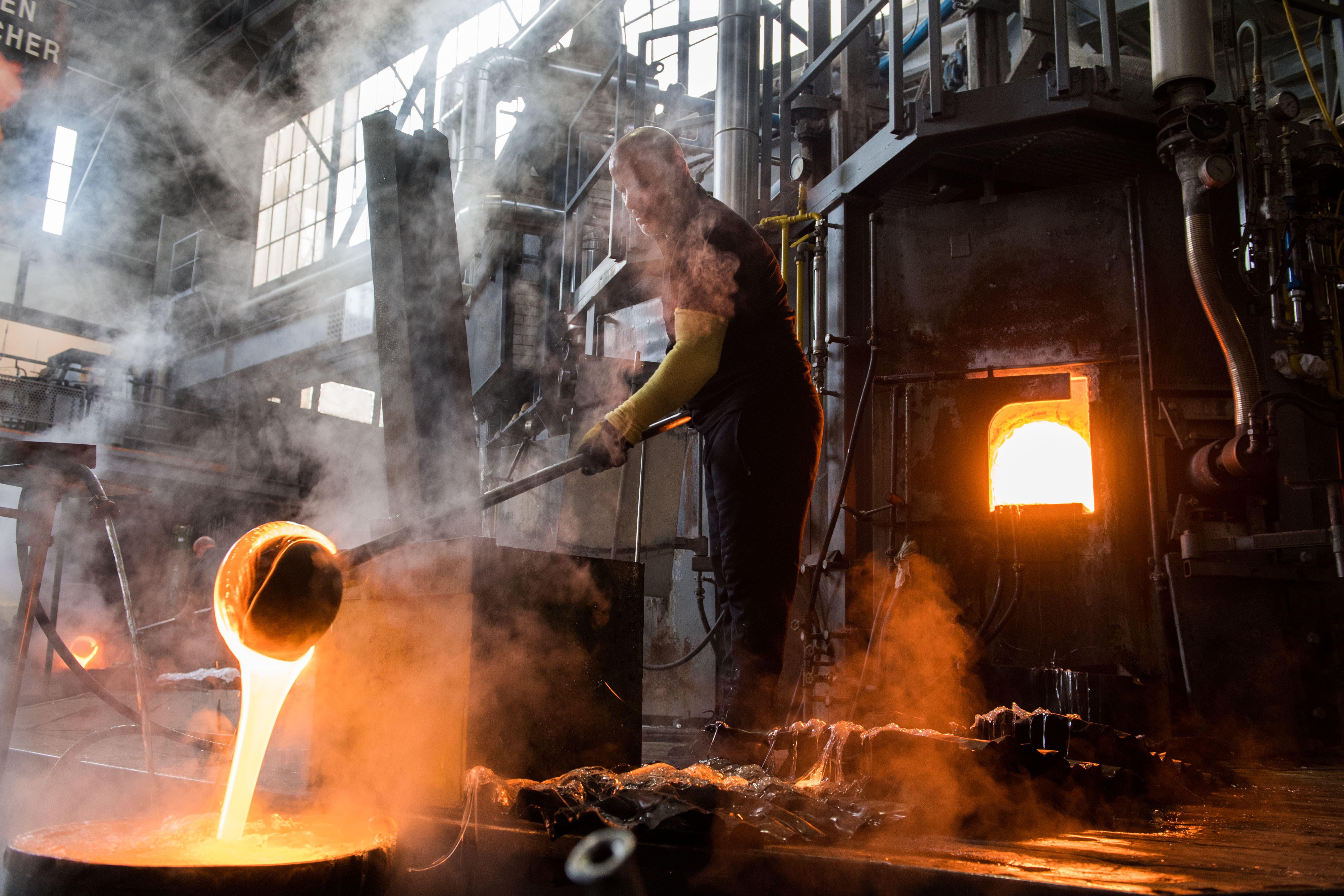 Mitarbeiter schöpfen auch von Hand Glas aus dem Ofen in einen mit Wasser gefüllten Tank ab.