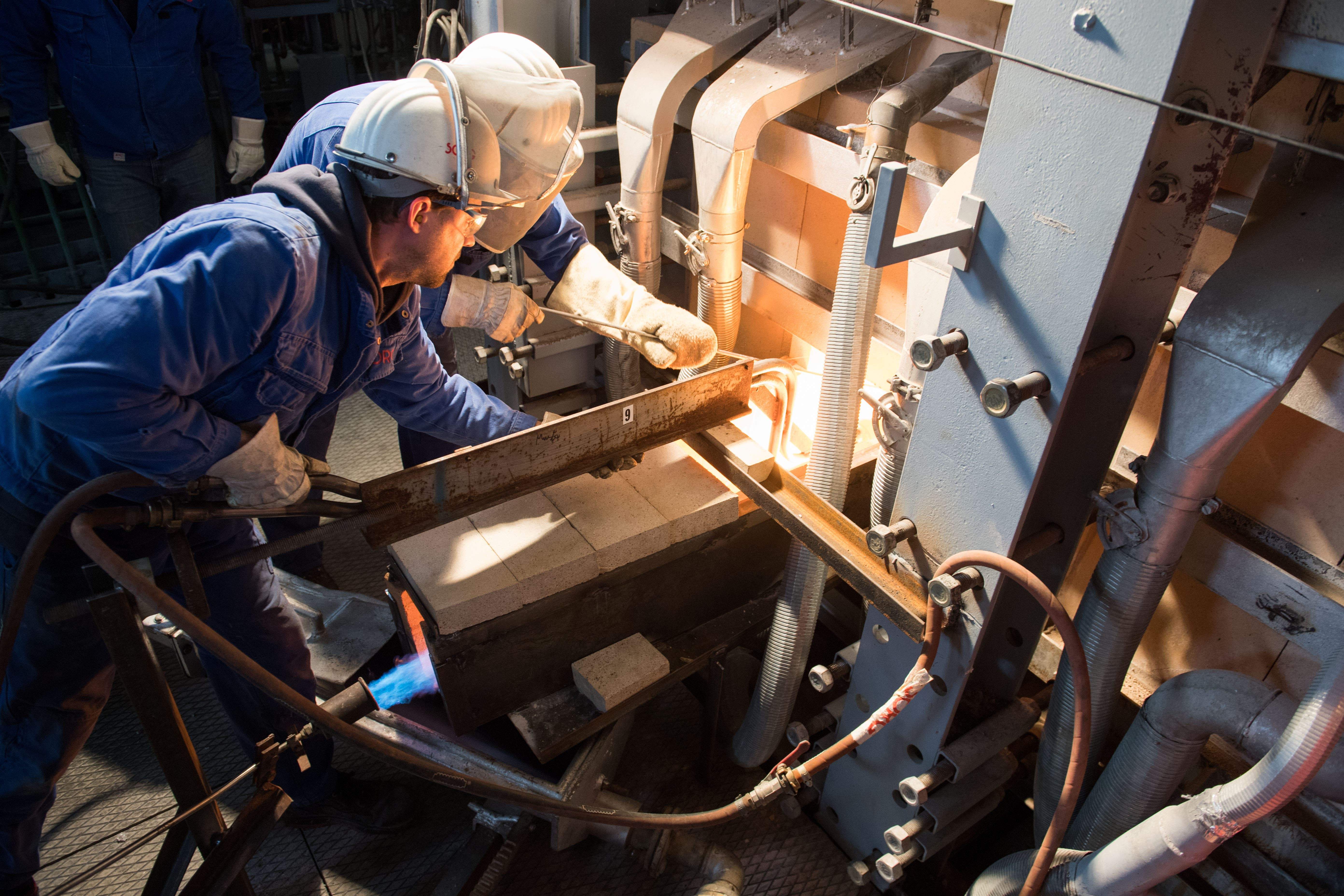 Spezialisten des deutschen Glasofenherstellers Sorg bereiten das Ablassen des flüssigen Glases vor.