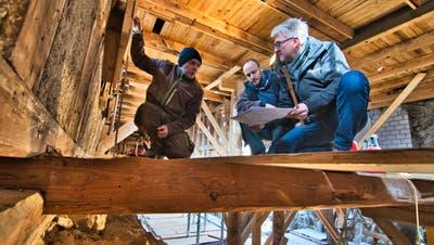 Oben Restaurant, unten Schlosshof: Architekt Thomas Kaczmarek (r.) und Schlossherr Andi Angehrn (m.) schauen sich mit Zimmermann Christian Camen (l.) die Baupläne an und besprechen das weitere Vorgehen. ((Bild: Manuel Nagel))