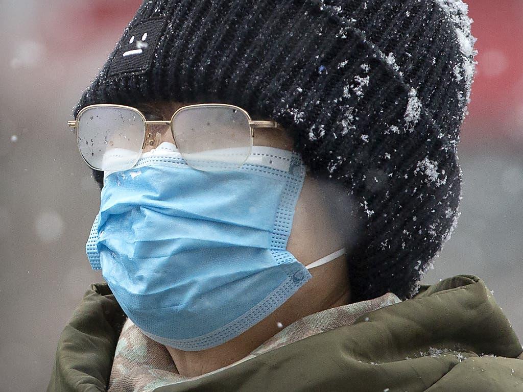 Bei Schneefall ist der Mundschutz eher hinderlich. Und doch schützen sich die Chinesen damit vor der Ansteckung durch das Coronavirus.