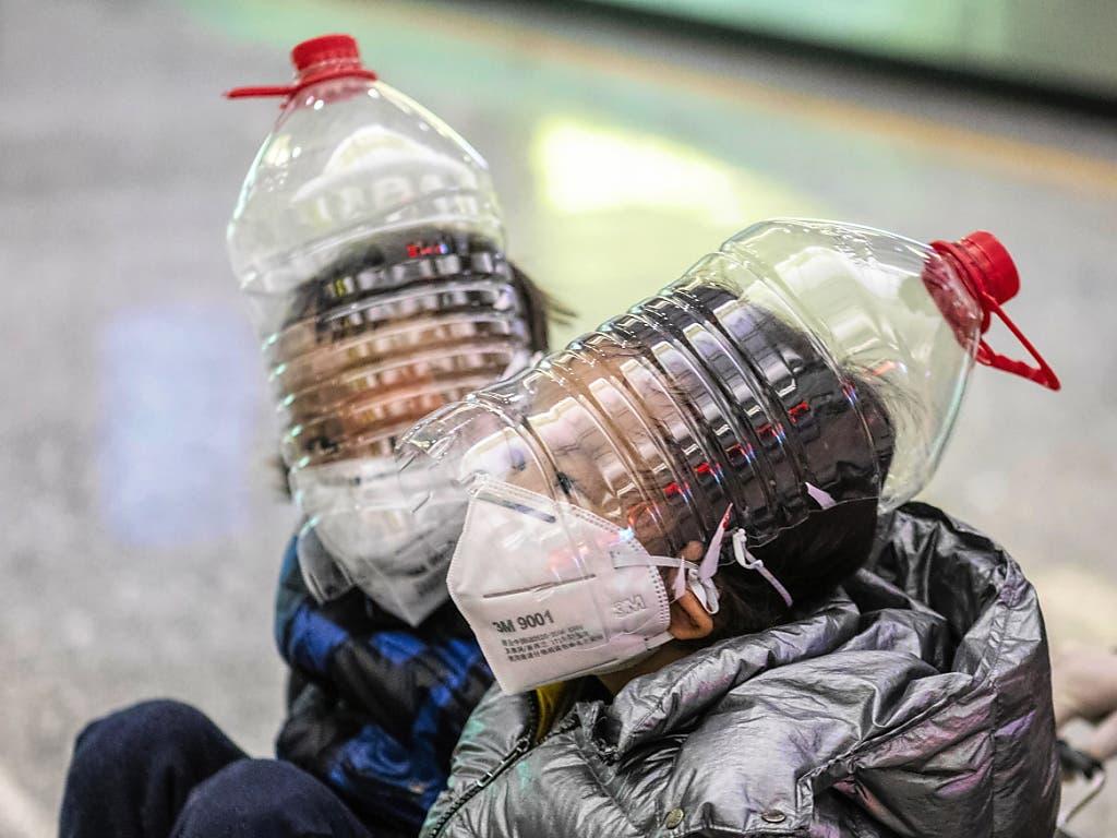 Zwei Kinder schützen sich am Flughafen von Guangzhou (China) vor der Ansteckung durch den Coronavirus.
