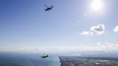Das ehemalige Flugzeug der Schweizer Luftwaffe hängt unter dem Helikopter über dem Bodensee. (Bild: Raphael Rohner)