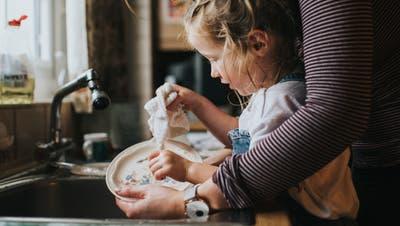 Eine Mutter hilft ihrem Kind beim Abwasch. (Bild: Getty)