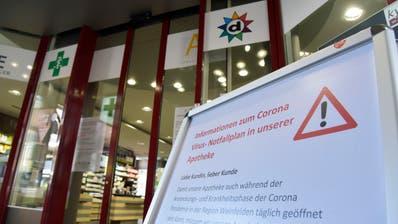 Auf Tafeln vor dem Eingang informiert die Apotheke Drogerie Aemisegger über die Massnahmen. ((Bild: Mario Testa))