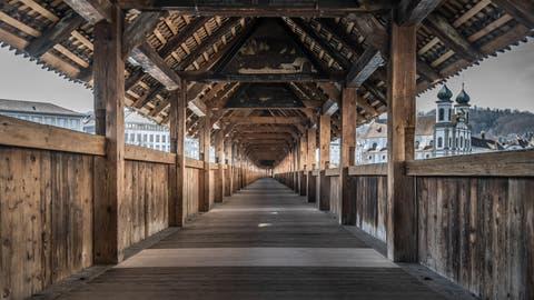 Die Pandemie hinterlässt ihre Spuren - auch auf Luzerns Wahrzeichen. Die Kapellbrücke präsentierte sich am Montag um die Mittagszeit menschenleer. (Bild: Pius Amrein (Luzern, 16. März 2020))