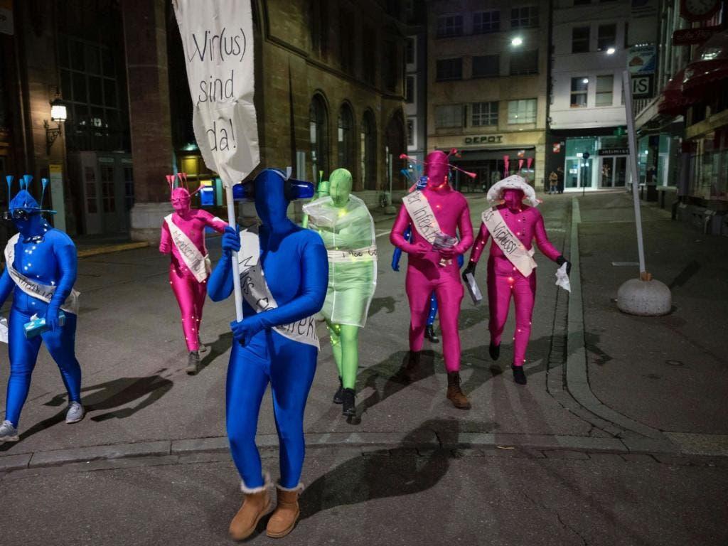 Eine als Virus verkleidete Gruppe marschiert zum nicht stattfindenden Morgestraich durch die Stadt Basel. (KEYSTONE/Georgios Kefalas)