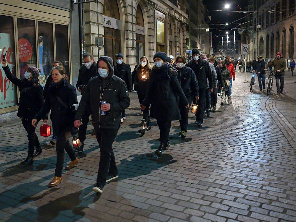 Fasnächtler ziehen mit Mundschutz und Kerzen durch die Gassen am nicht stattfindenden Morgestraich in Basel (KEYSTONE/Georgios Kefalas)