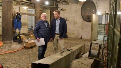 Bruno Mästinger und Stefan Haffter im Weinkeller mit den demontierten Lüftungsrohren und temporären Stromleitungen. ((Bild: Mario Testa))