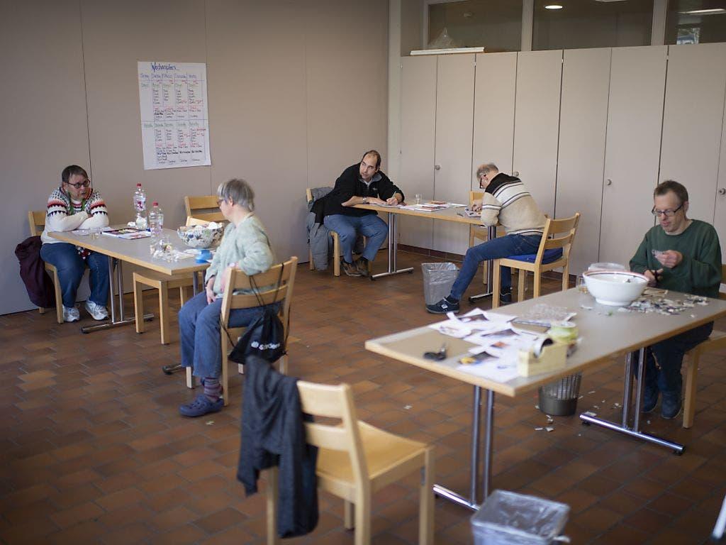 Beschäftigung und klare Tagesstrukturen sollen den Bewohnern der Valida helfen, die Corona-Krise besser zu bewältigen: Ein Gruppe von Menschen mit Beeinträchtigung arbeitet in St. Gallen in einem Atelier an Geschenkverpackungen für Weihnachten.